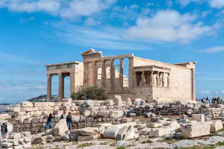 Athens, Greece - November 1, 2017: Tourists visit the Erechtheion temple in Acropolis of Athens, an ancient citadel located on a rocky outcrop above the city and famous landmark in Athens, Greece.
