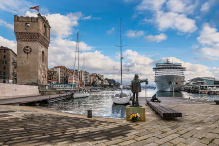 Savona, Italy - December 2, 2016: The cruise ship Costa Deliziosa of the Italian company Costa Crociere is docked in front of a fisherman statue in the harbour of Savona in Liguria, Italy.
