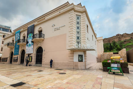 Malaga, Spain - December 7, 2016: View on the Albeniz cinema in pedestrian zone of Alcazabilla street before the rain in downtown of Malaga, Andalusia, Spain.