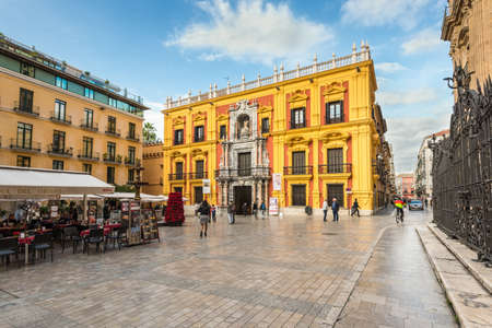 Malaga, Spain - December 7, 2016: Episcopal palace facade and tourist sitting on the restaurants terraces and walking around Bishop Square in Malaga city center, Andalusia, Spain.