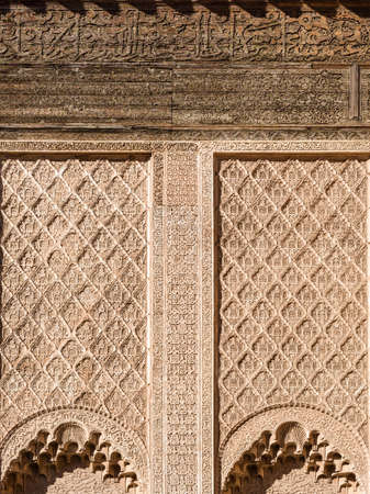 Ali ben Youssef Madrasa exterior islamic symbols, calligraphy and sacred geometry carved on the wall in Marrakesh, Morocco