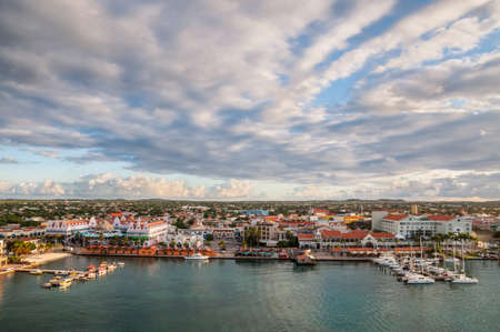 Oranjestad, Aruba - December 1, 2011: View of Oranjestad, capital of Aruba. Small boats and yachts are moored to the jetty and white Dutch style buildings are in the middle. The skyline of Oranjestad, capital of Aruba.