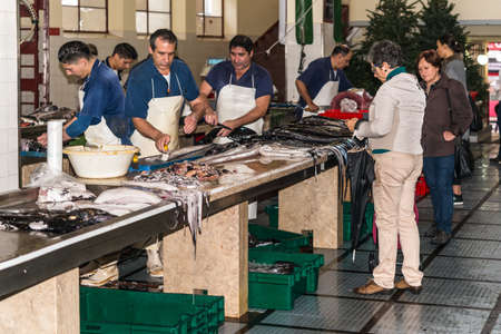 Funchal, Portugal - December 10, 2016: Buyers and sellers of seafood and fish in the Funchal Fish Market Mercado dos Lavradores in Madeira Island, Funchal, Portugal.