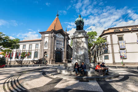 Funchal, Portugal - December 10, 2016: People are resting at the foot of the Joao Goncalves Zarco statue in front of the bank of Portugal in Funchal, Madeira Island, Portugal. Editorial