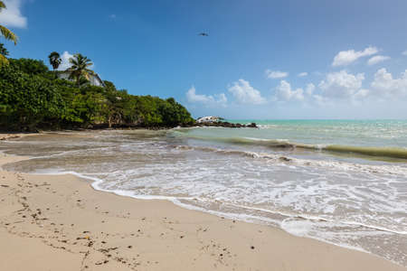 Paradise tropical beach, the Gosier in Guadeloupe island, Caribbean. A Sailboat was destroyed and abandoned on the shore after a hurricane. Stock Photo