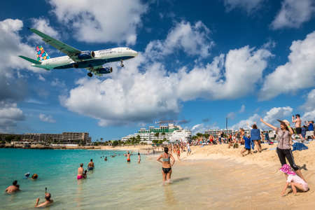 Maho beach, Saint Martin - December 17, 2018: A commercial jet approaches Princess Juliana airport above onlooking spectators. The short runway gives beach goers close proximity views of the planes.