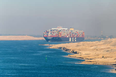 El Qantara, Egypt - November 5, 2017: Large container vessel ship MSC Maya passing Suez Canal in the sandy haze in Egypt.