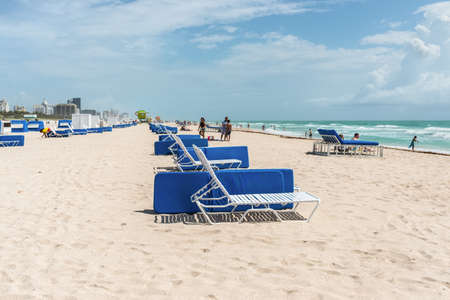 Miami, FL, USA - April 19, 2019: Sandy South Miami, Beach with sun loungers and people relaxing under cloudy blue sunny sky. Sunbathing and swimming concept. Recreation, relax and lounge.