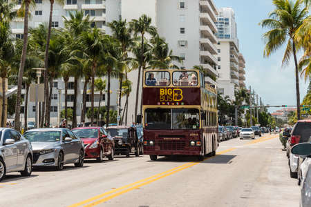 Miami, FL, United States - April 19, 2019: Double decker Big Bus Miami Hop-on Hop-off bus tours are a popular way to see the city. This one is cruising Ocean Drive, Miami Beach, Florida, United States of America.