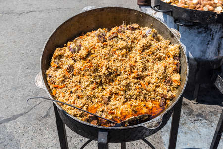 Traditional dish of oriental cuisine - pilaf with meat in a larger vat on the street during the festival