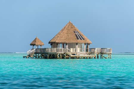 Wasserbungalow und blaues türkisfarbenes Meer in einer tropischen Paradiesinsel auf den Malediven