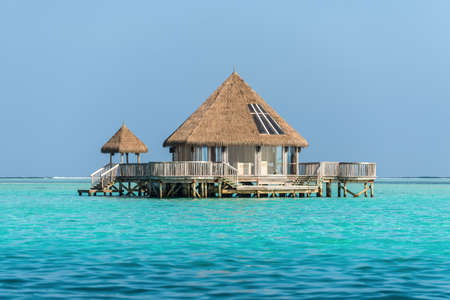 Water bungalow and blue turquoise sea in a tropical paradise island in Maldives