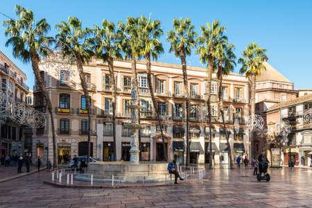 Malaga, Spain - December 4, 2018:  Shady Constitution Square (Plaza de la Constitucion de Malaga) decorated for Christmas in downtown of Malaga, Andalusia, Spain.