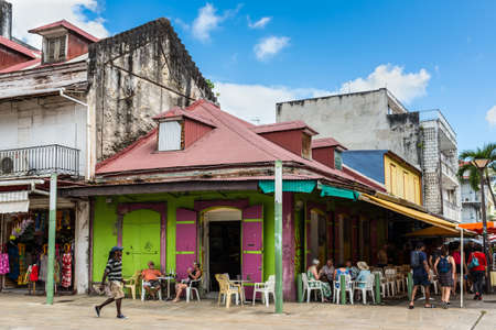 Pointe-a-Pitre, Guadeloupe - December 14, 2018: People have a rest in cafe on the square, style of life in Pointe-a-Pitre, in the French overseas department of Guadeloupe.