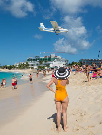 Maho beach, Saint Martin - December 17, 2018: A airplane approaches Princess Juliana airport above onlooking spectators. Woman on cruise ship vacation travel relaxing in famous touristic destination. Editorial