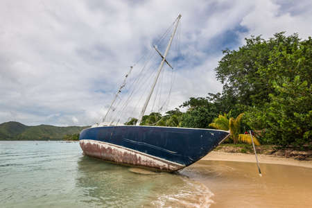 Abandoned beached sailboat after the hurrican Maria at the beautiful tourist beach at Sainte-Anne in Martinique, Caribean island in cloudy weather - ship wreck on the shore of the beach