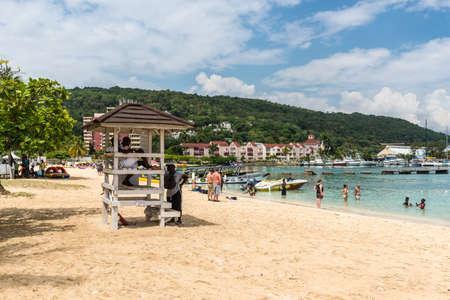 Ocho Rios, Jamaica - April 22, 2019: Ocho Rios Bay Beach with lifeguard tower and people relaxing on the beach in Ocho Rios, Jamaica. 新聞圖片