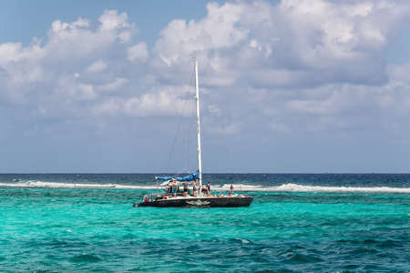 George Town, Grand Cayman Islands, UK - April 23, 2019: Tourists on catamaran the Far Tortuga at Stingray city on Grand Cayman island, where stingrays are abundant and tourists have fun with the fish.