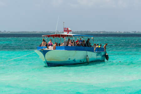 George Town, Grand Cayman Islands, UK - April 23, 2019: Tourists on a boat at wild Stingray city on Gran Cayman, Cayman islands, where stingrays are abundant and tourists have fun with the fish.
