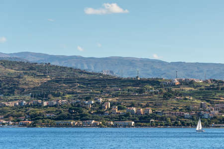 The Strait of Messina connected Mediterranean and Tyrrhenian sea and Sicilia island with blue sky and coast as background, view from promenade quay waterfront of Reggio di Calabria, Southern Italy