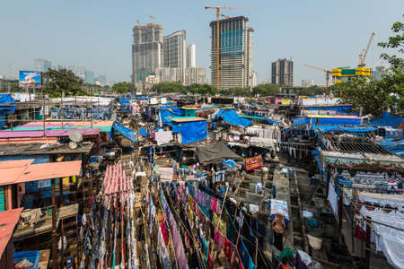 Mumbai, India - November 22, 2019: The Mahalaxmi Dhobi Ghat, or outdoor laundry, is considered to be the largest of its kind in the world. The historic Dhobi Ghat contrasts with the tall buildings. Redactioneel