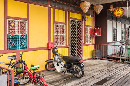 George Town, Penang, Malaysia - December 1, 2019: Bike and bicycles on wooden sidewalk of the famous local fishing village Clan Lee Jetty in George Town, Penang, Malaysia.