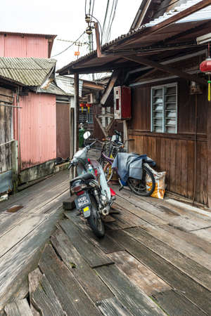 George Town, Penang, Malaysia - December 1, 2019: Motorcycle and bicycles on wooden sidewalk of the famous local fishing village Clan Tan Jetty in George Town, Penang, Malaysia.