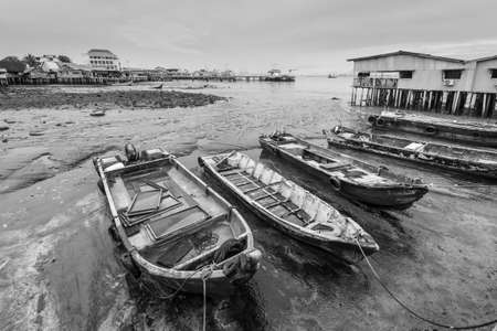 Harbor view from one of the Clan Jetties in historic George Town, Penang, Malaysia - Chew Jetty. Wooden boats moored at low tide in cloudy rainy weather. Black and white photography for printing.