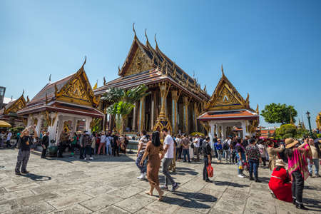 Bangkok, Thailand - December 7, 2019: Many tourists in the Wat Phra Kaew - the Temple of Emerald Buddha in Bangkok, Thailand.