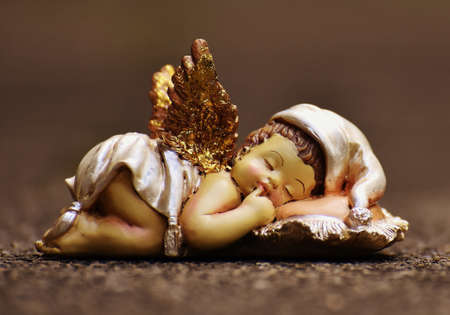 Sleeping little angel with golden wings on a dark background Stock Photo