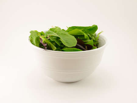 Mixed Salad Greens in a White bowl isolated on a white background