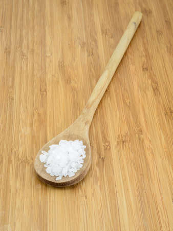 Sea salt crystals in a wooden spoon against a bamboo background