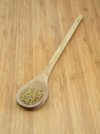 A pile of cumin seeds in a wooden spoon against a bamboo background Reklamní fotografie