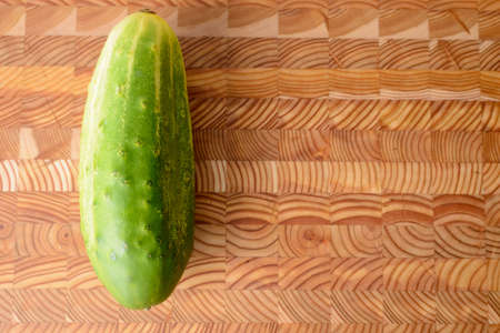 Single cucumber on a wooden cutting board