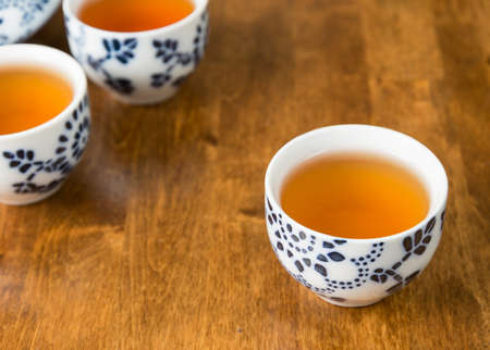 teacups: Teacups filled with tea on a wooden table.