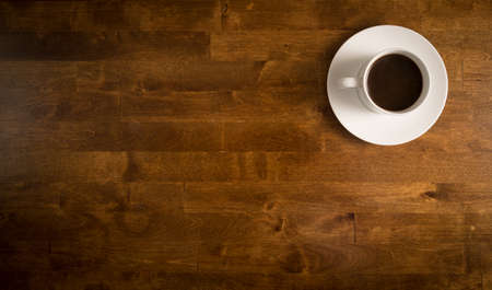 office desk: Coffee in white cup on a saucer on a wooden table