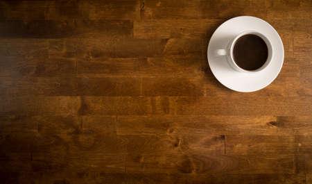 Koffie in witte kop op een schotel op een houten tafel