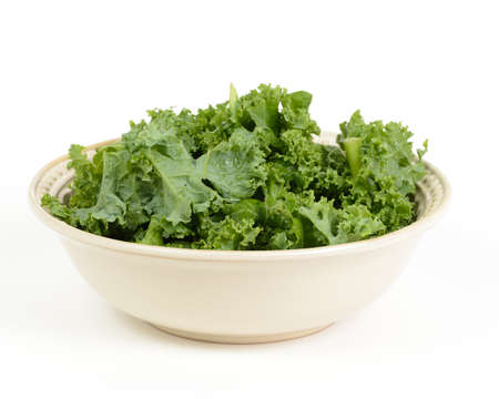 Chopped kale salad in a bowl isolated on a white background.