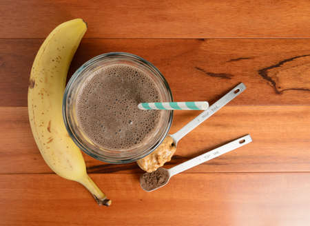 Chocolate banana smoothie in a glass on a wooden table.