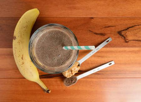 licuado de platano: Chocolate batido de plátano en un vaso sobre una mesa de madera.