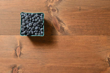 A bunch of blueberries in a carton on a wooden table shot from above