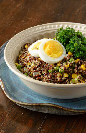 Quinoa bowl filled with broccoli, corn, peas, and hard boiled egg.