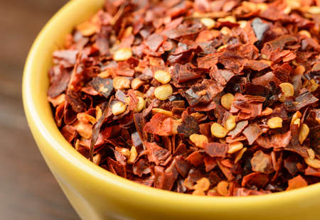Close-up of crushed red pepper in a yellow bowl. Stock Photo