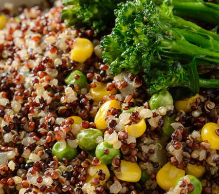 A close up of a quinoa bowl with broccoli, corn, and peas