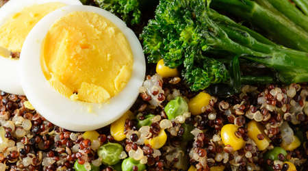 A close up of a quinoa bowl with broccoli, egg, corn, and peas Imagens