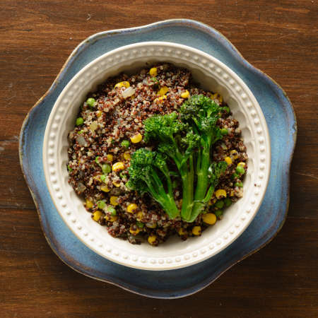 Quinoa bowl filled with broccoli, corn, peas, and onions