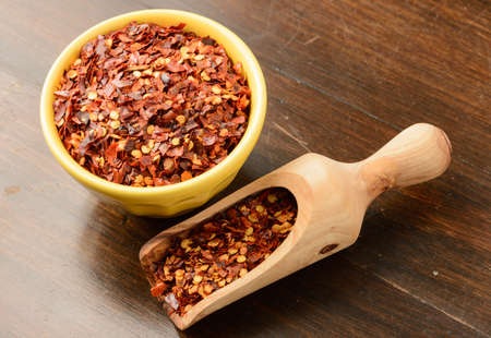 crushed red peppers: Crushed red pepper flakes with a wood scoop.