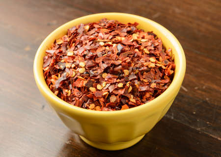 Crushed red pepper in a yellow bowl Stock Photo