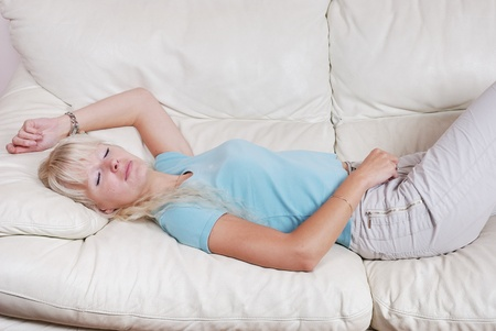 Blond woman resting  on a sofa photo