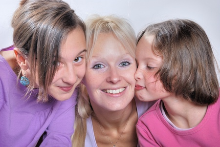 A mother smiles as she receives a kiss on the cheek from her young daughters photo